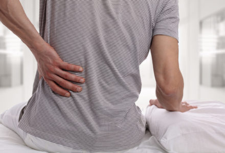 Man sitting on a bed holding his back from pain