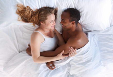 Young romantic couple hugging in bed