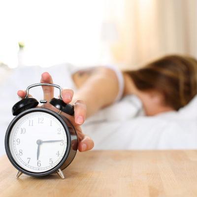 Sleepy woman trying to kill alarm clock