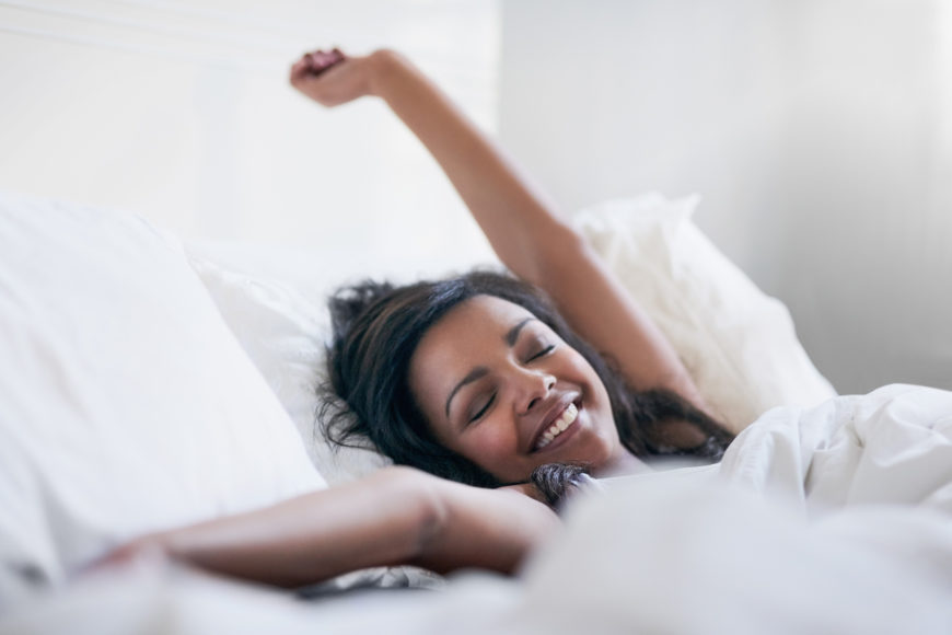 Happy woman waking up in her mattress