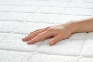 Hand feeling a mattress