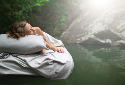 Sleeping woman on mattress floating on water