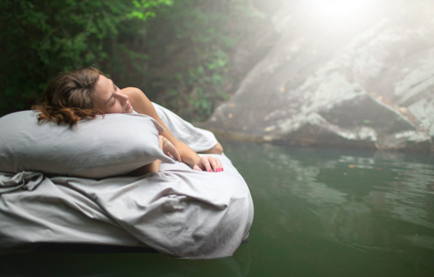 Sleeping woman on mattress floating on water