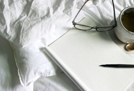 Blank notebook, eyeglasses, cup of tea on white unmade bed