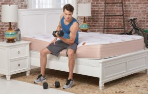 Man lifting weights on the PangeaBed mattress in his bedroom