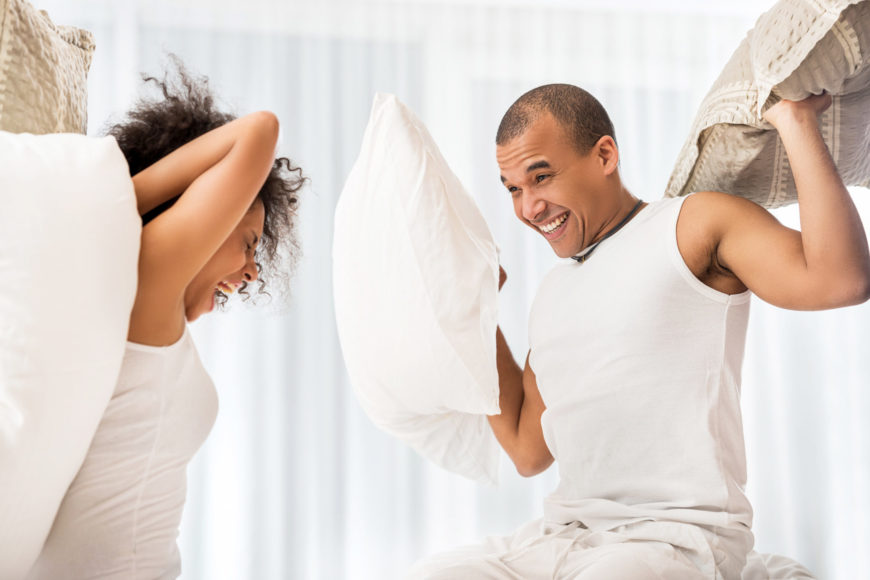 Couple having a pillow fight on a mattress