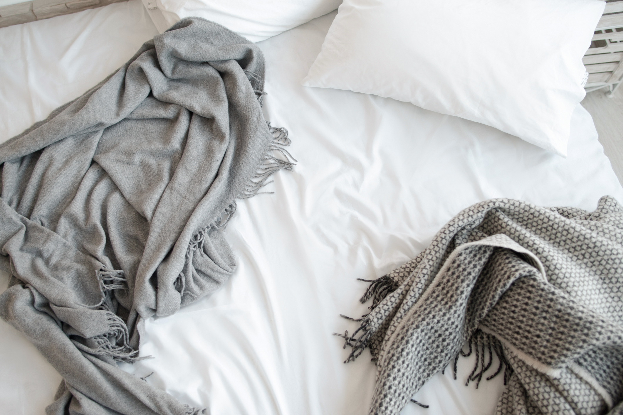 Messy bed with blanket and pillows