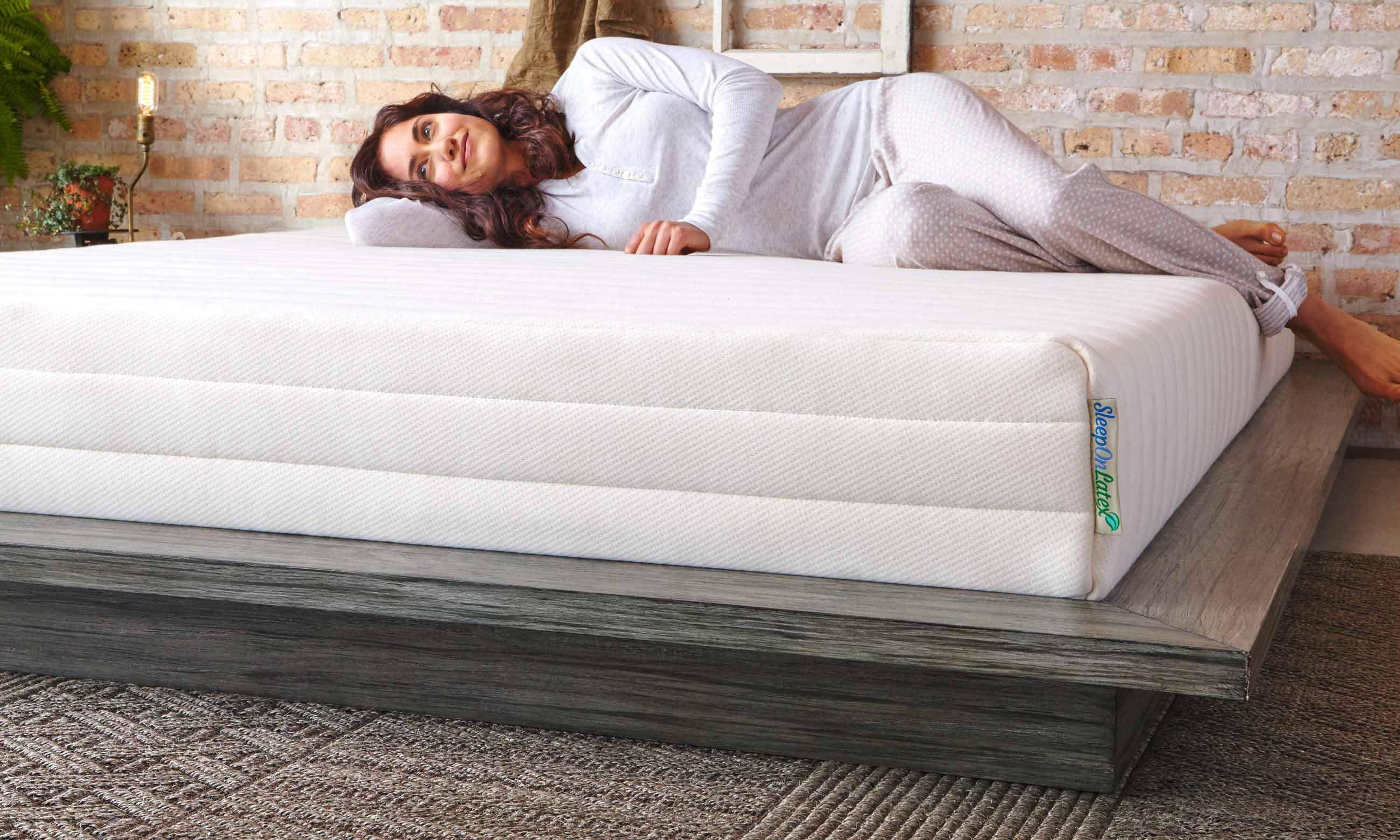 Woman lying down on Pure Green mattress by SleepOnLatex