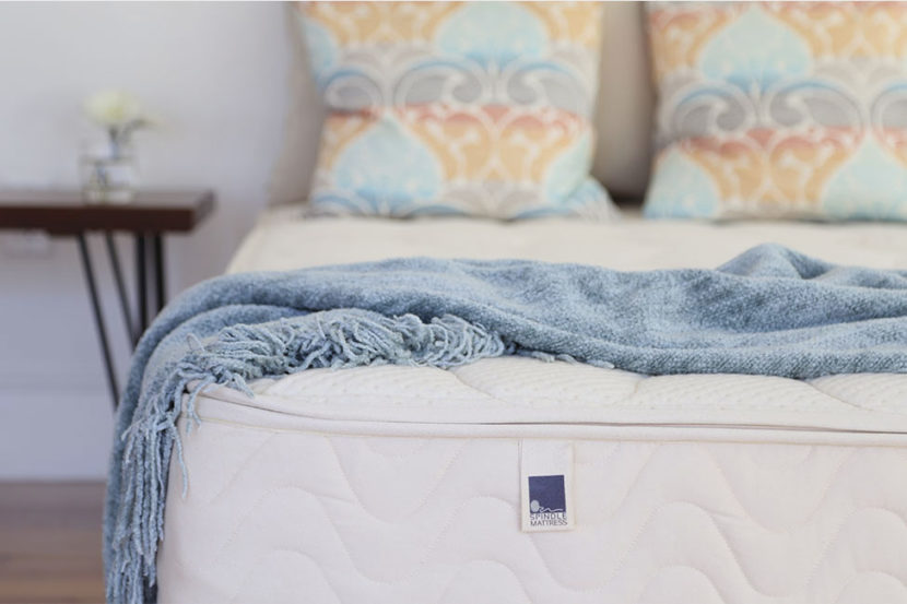 Spindle mattress in a bedroom with light blue blanket across the top