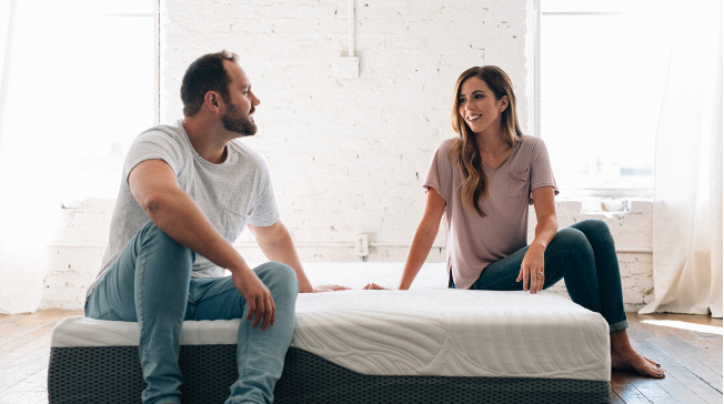 Young couple sitting on top of Voila mattress