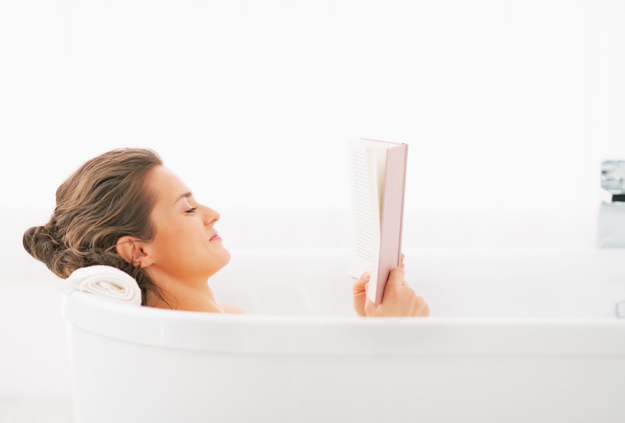 Young woman reading book in bathtub