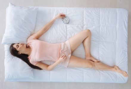 Woman lying on mattress with a clock