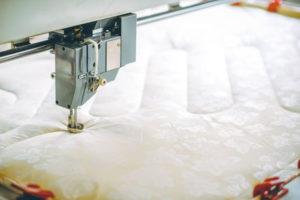 sewing machine stitching a mattress