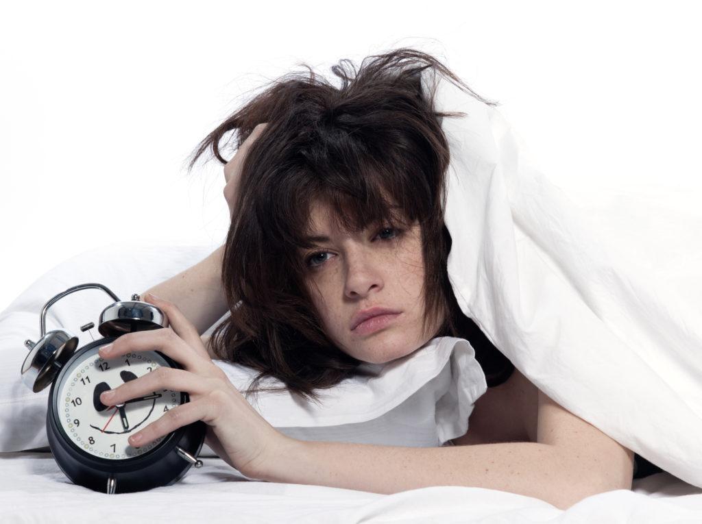 Sleep deprived woman waking up