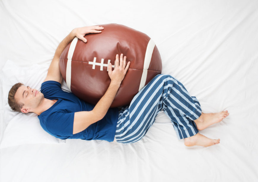 Man sleeping with football