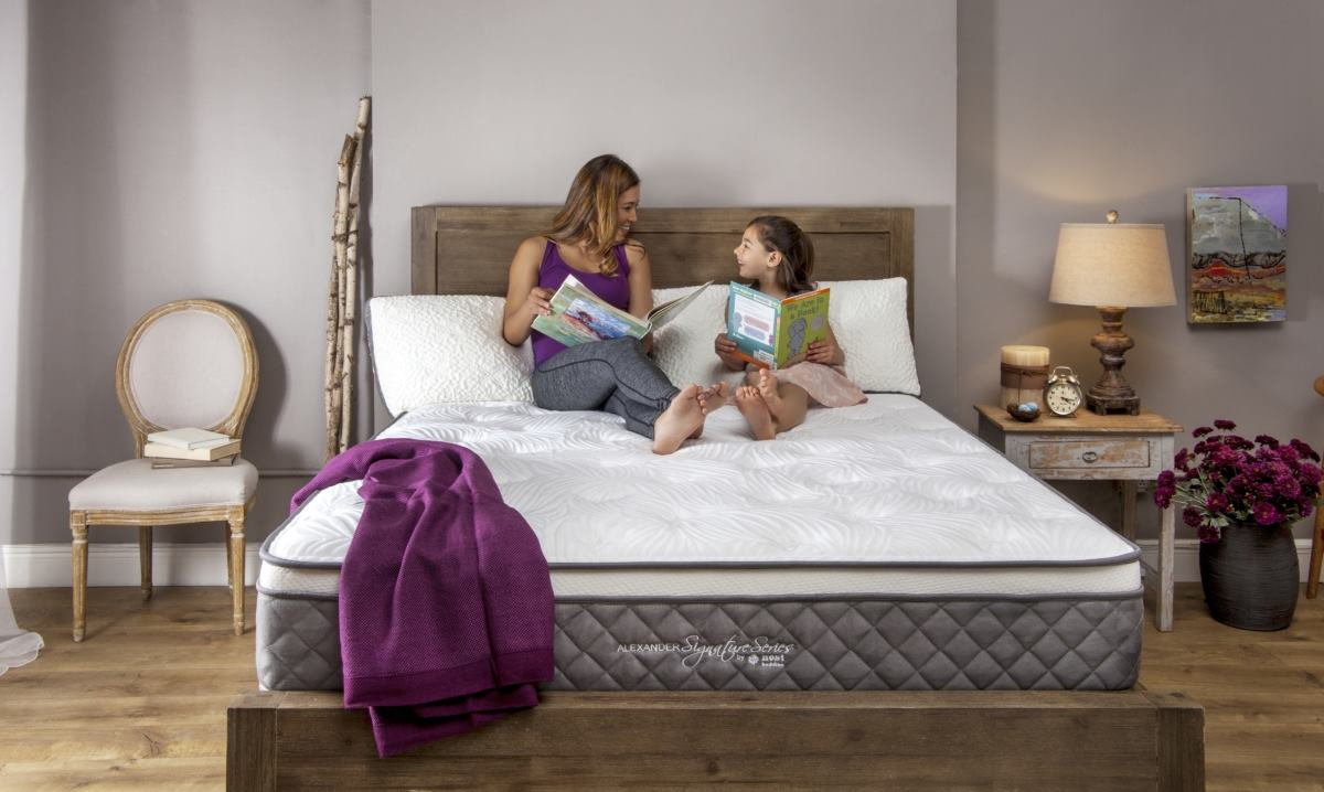 Mom and daughter sitting on the Alexander Signature Series mattress in a bedroom.