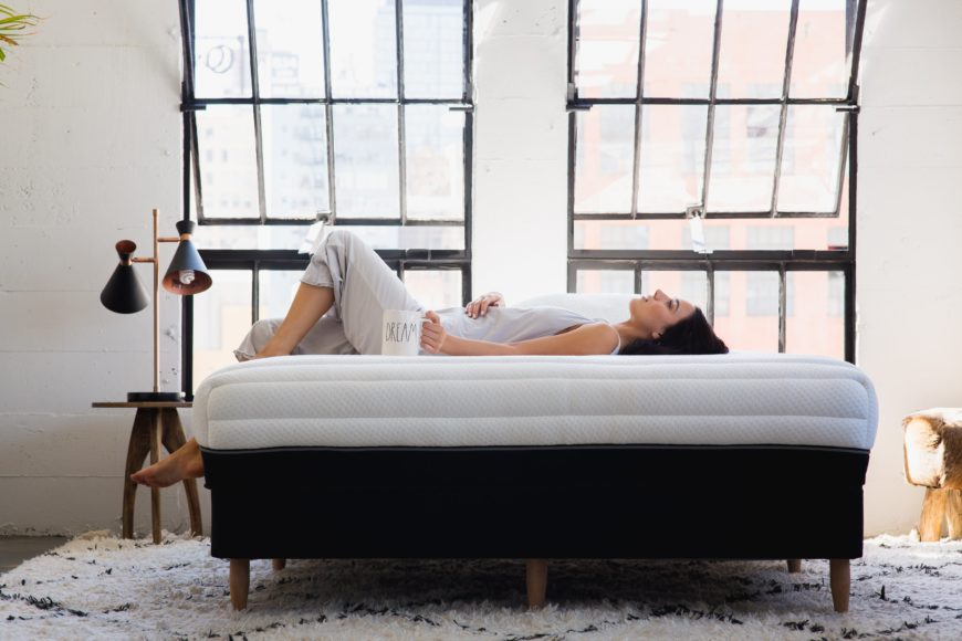 Woman laying on the Luxi mattress in a city apartment