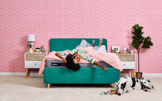 Woman lying on the New Purple Mattress in a pink bedroom