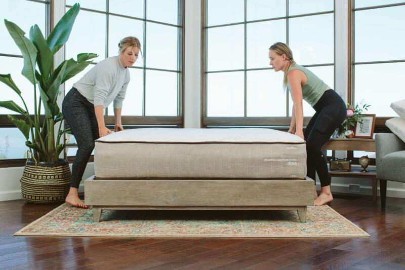 man and woman setting up mattress