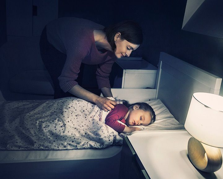 Mother tucking child in at night
