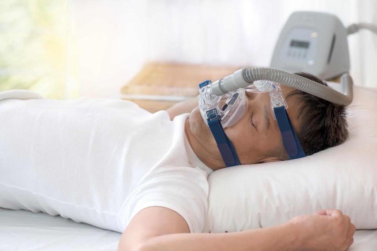 Sleep apnea therapy, Man sleeping in bed wearing CPAP mask.