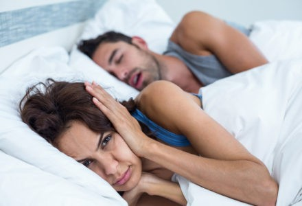 Portrait of woman blocking ears with hands while man snoring on bed