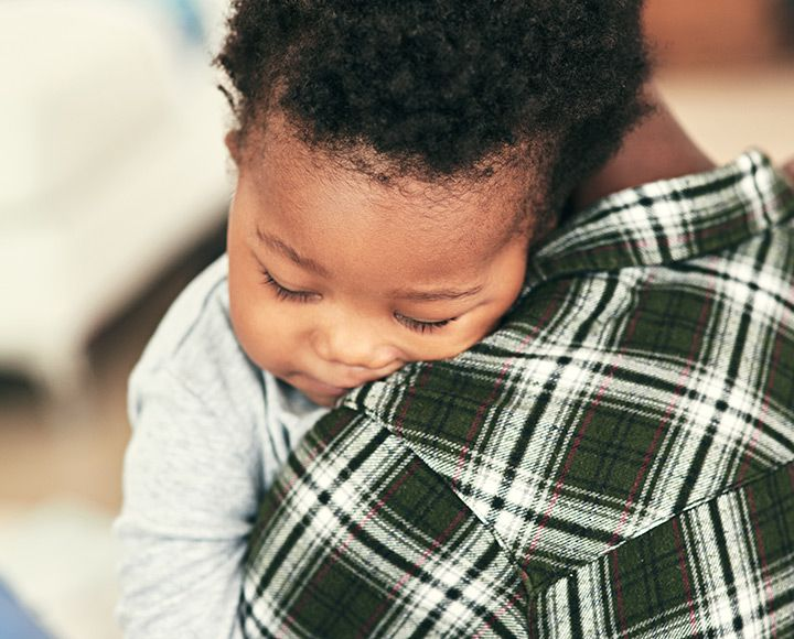 Baby sleeping on dad's shoulder
