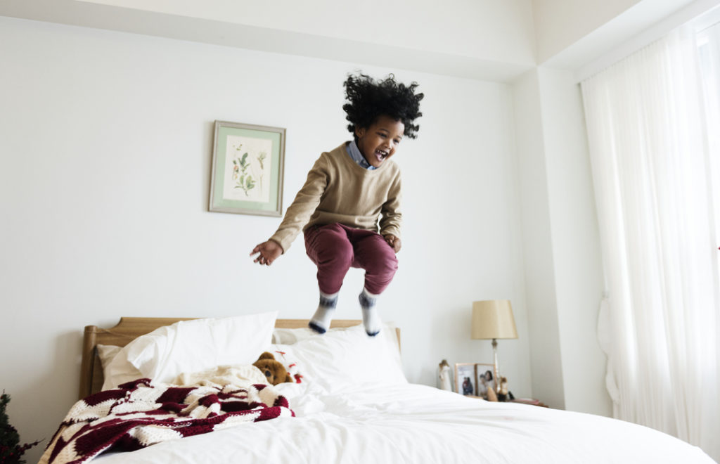Kid jumping on a bed