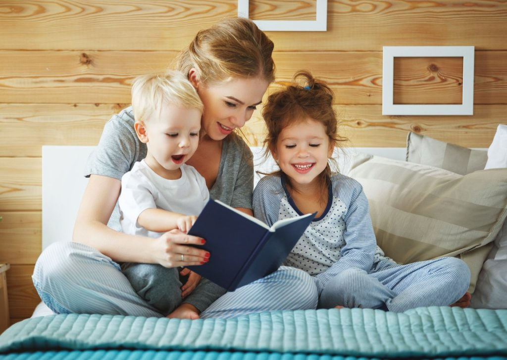 Mother reading children book in bed