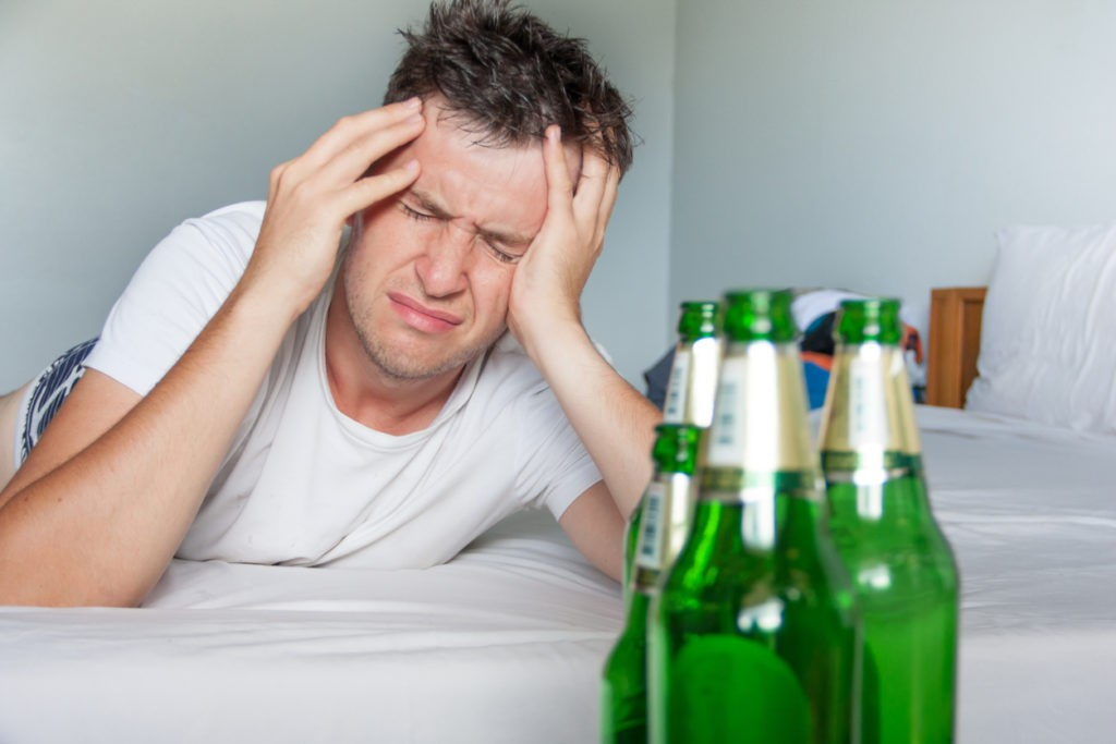 Hangover suffering man close up portrait with bottles of beer.