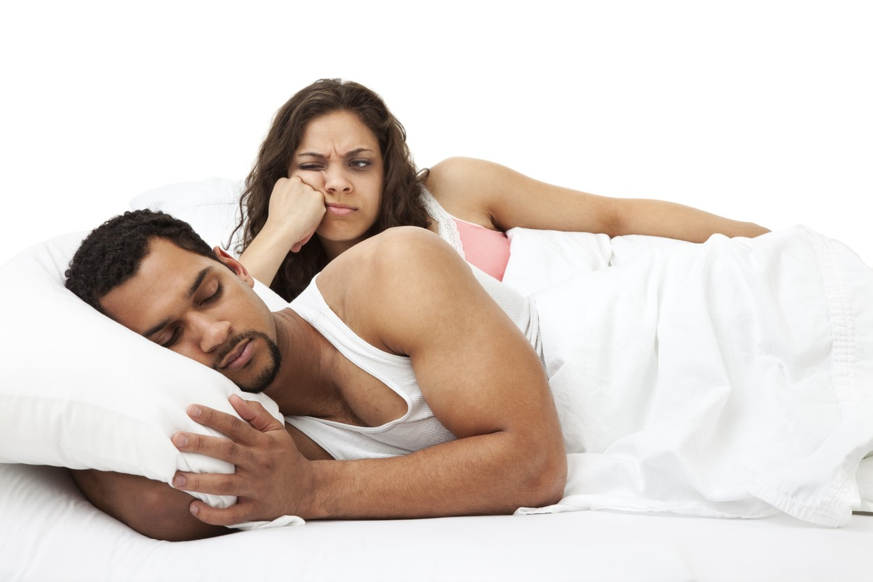 Photo of an attractive young couple in bed. Woman is looking at her husband as he sleeps with a frustrated expression on her face.