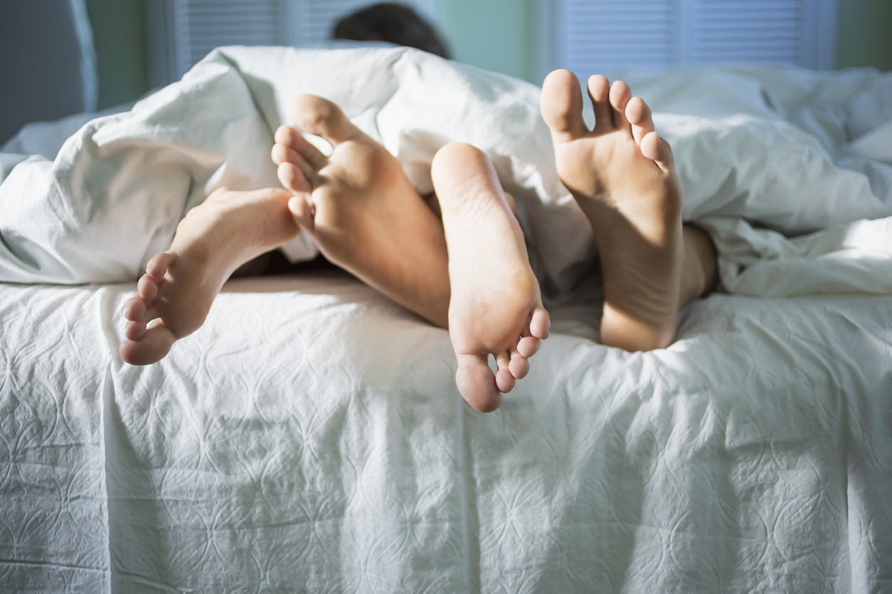 The soles of the feet of a young couple sticking out from under the blankets at the foot of the bed. They are entwined, with the toes of the man pointing up and the toes of the woman pointing downward. The sheets and blankets are white.