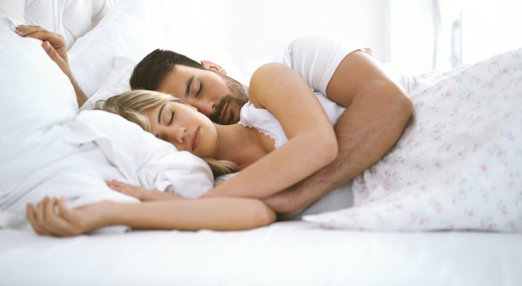 Closeup side view of mid 20's couple comfortably sleeping in bedroom. They are embraced and facing camera.