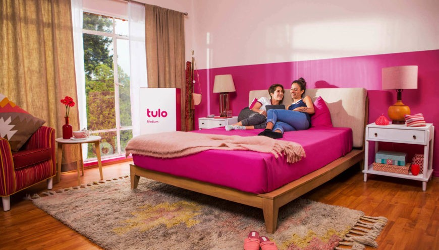 Tulo Mattress in a pink bedroom with two friends chatting on the bed.