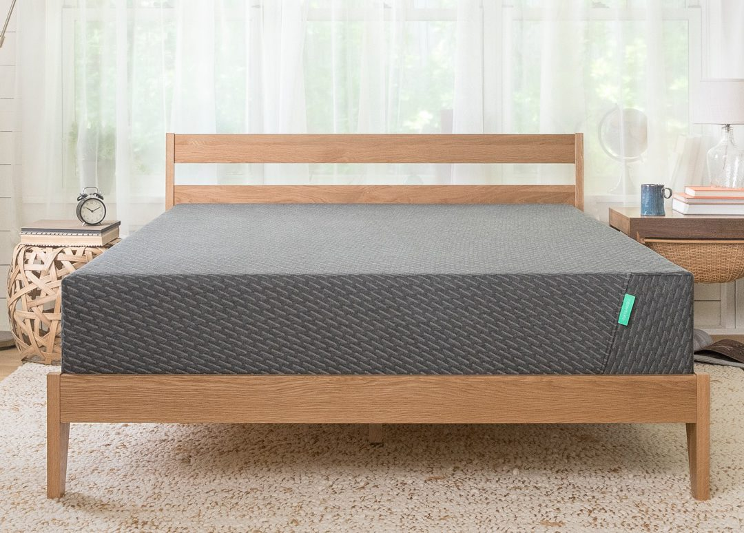 Tuft and Needle Mint mattress on a wooden bed frame in a bedroom