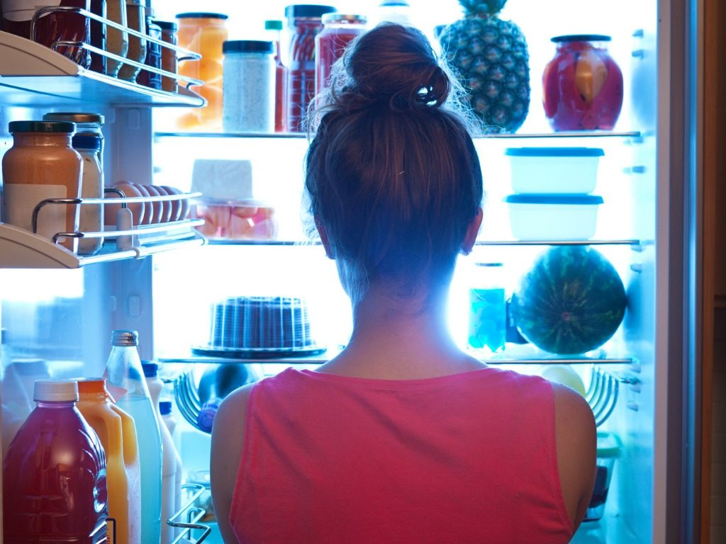 woman contemplating midnight snack late night with open refrigerator