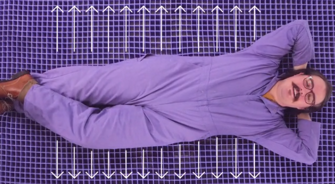 Purple's brand character, the Sleepy Scientist, laying on a Purple mattress