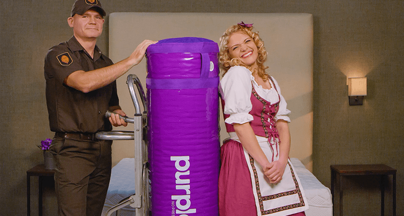 Purple's brand character, Goldilocks, standing beside the UPS guy who is delivering a Purple Mattress