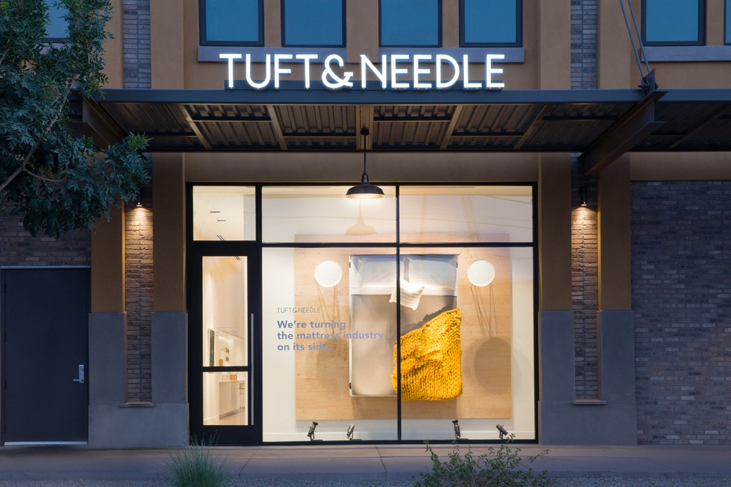 A street side view of the Tuft & Needle Gilbert, AZ store at dusk.