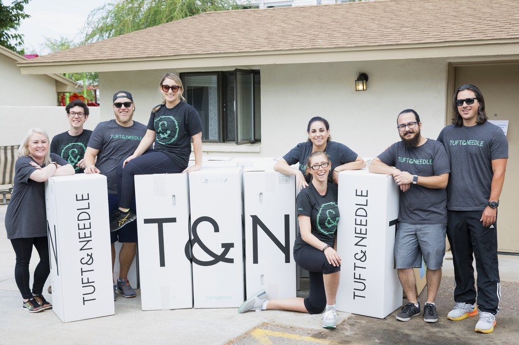 A photo of Tuft & Needle teams members posing with Tuft & Needle mattress boxes.