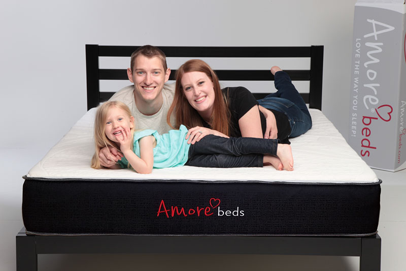 couple and child on amore hybrid mattress