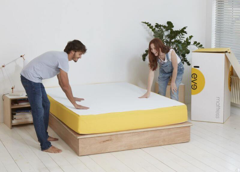 man and woman setting up a mattress