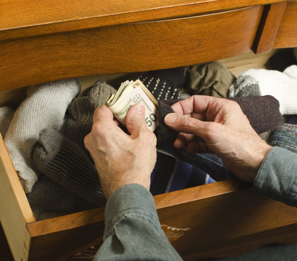 man hiding cash in sock drawer