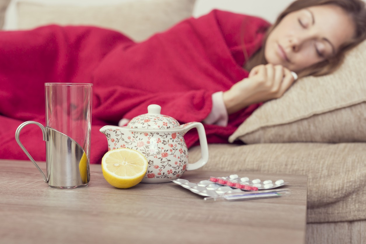 Sick woman covered with a blanket lying in bed resting. Teapot, pills and lemon on the table, focus on the lemon and a teapot