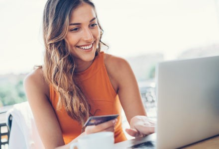 Beautiful young woman with credit card and laptop in cafe