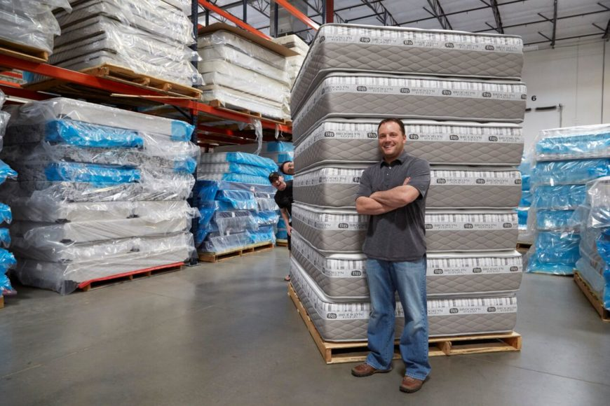 Founder of Brooklyn Bedding, John Merwin standing by his mattresses in his factory.