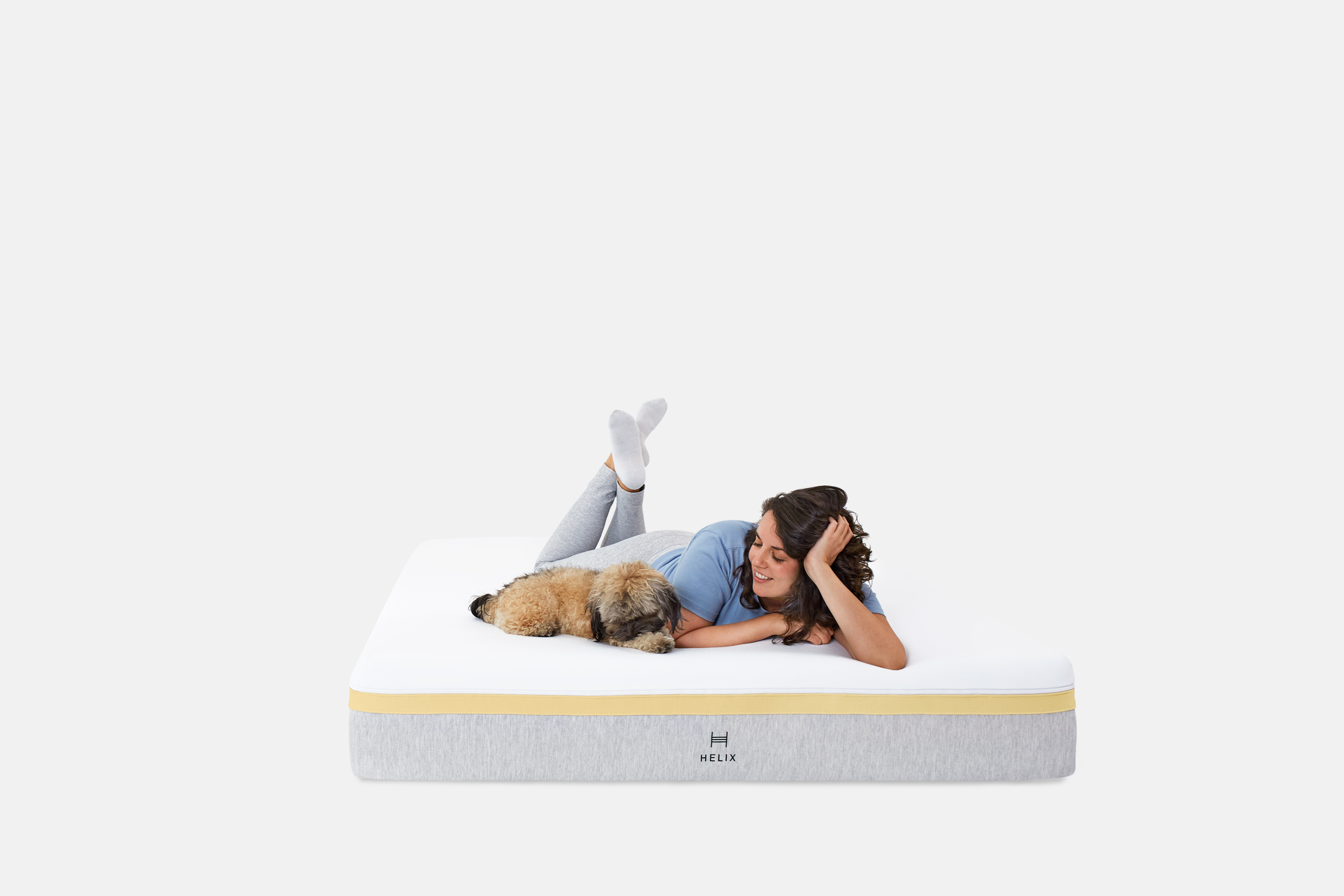 Woman laying on Helix mattress with her dog