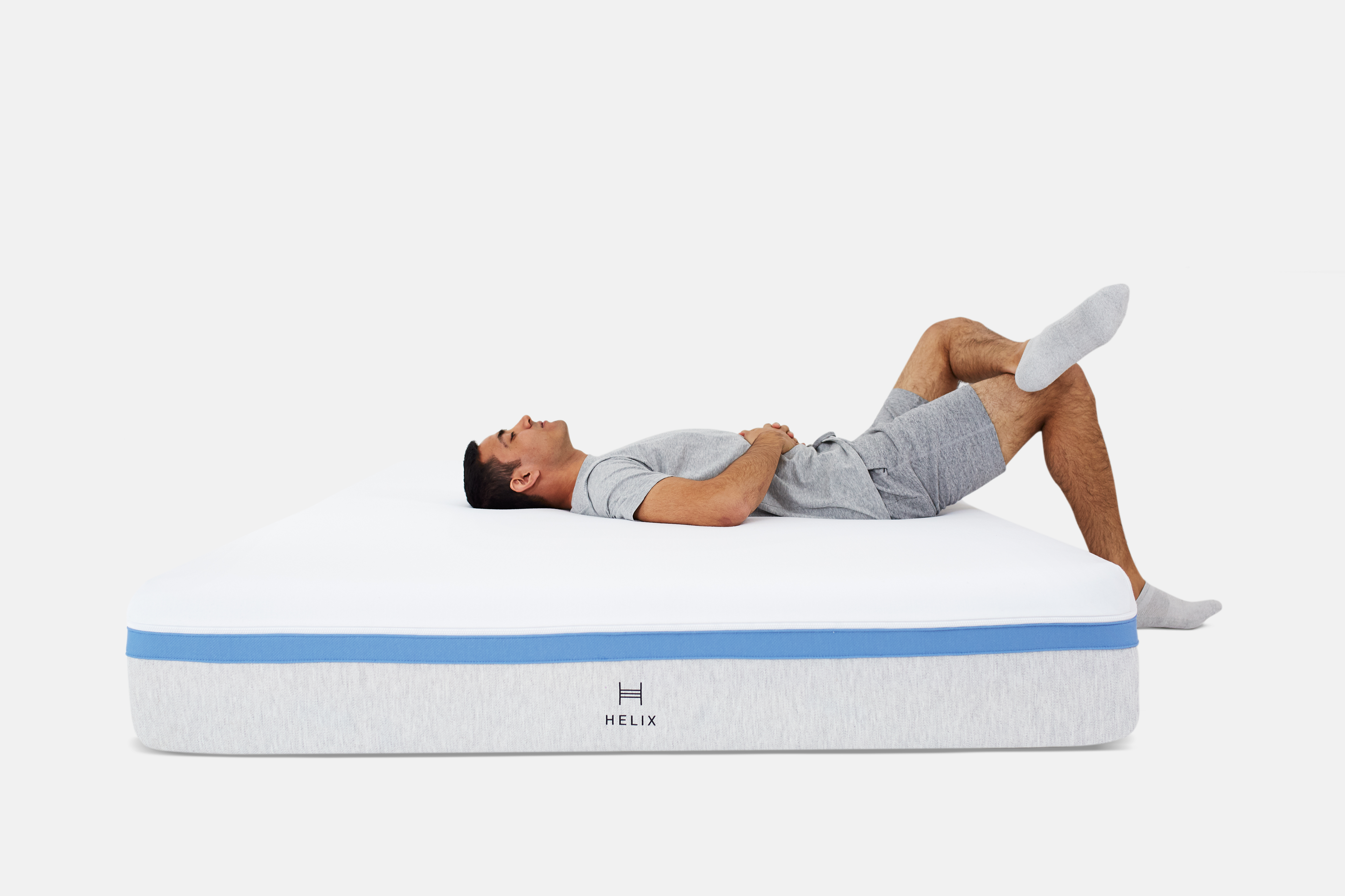 Guy laying on his back on the Helix mattress