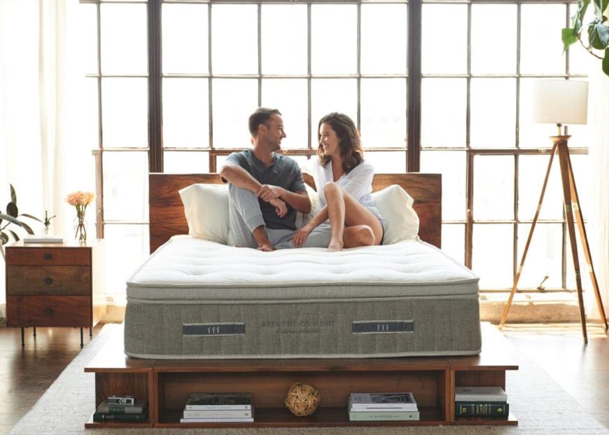 Cedar mattress in a bedroom with couple on it talking