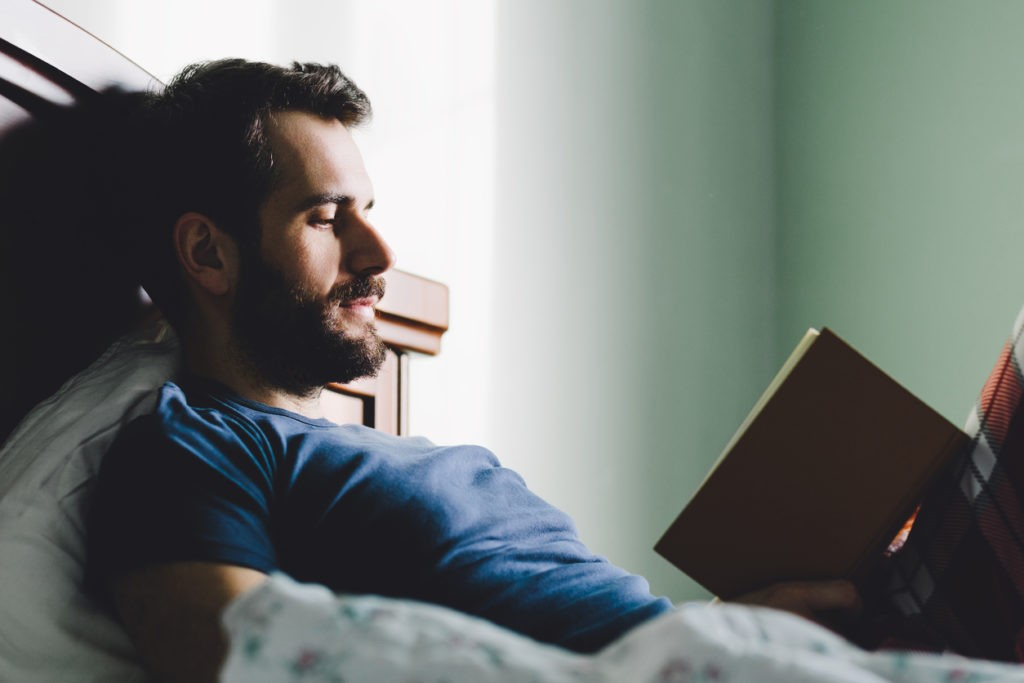 Young man reading a book before bed